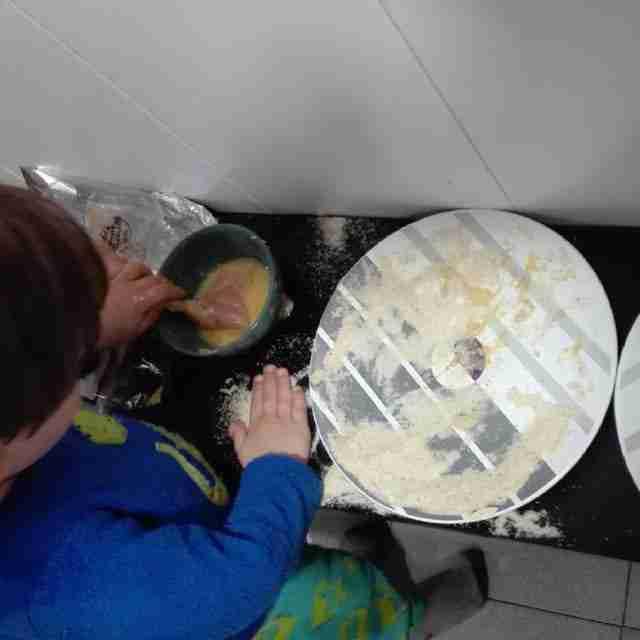 Cocinando con nios empanando pollo